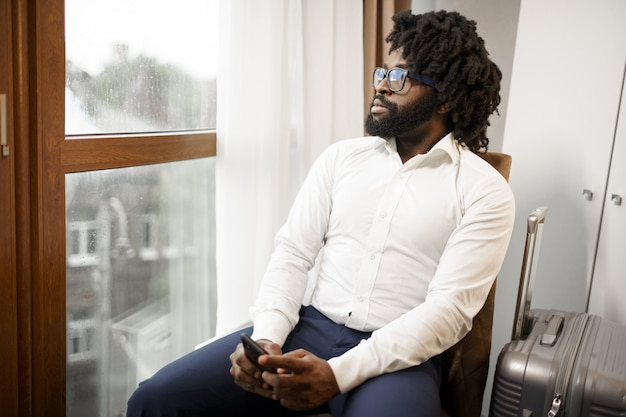 座っているとホテルの部屋の窓を見て黒人男性ビジネスマン