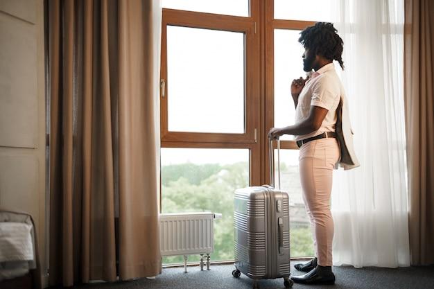 ホテルの部屋の大きな窓の近くに詰められたスーツケースと黒人男性ビジネスマンの肖像画