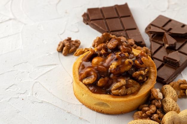 Пирог с орехами и шоколадом на белом фоне текстурированных