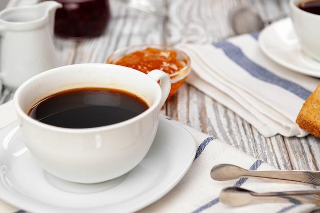 Белая чашка кофе на деревянный кухонный стол