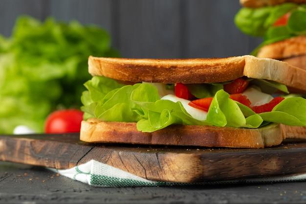 暗い背景の木に野菜とヘルシーなサンドイッチ