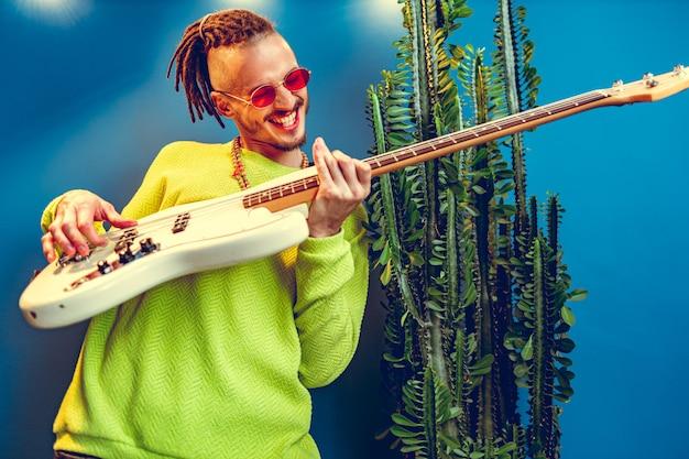 自宅でギターを弾くドレッドのクールな男