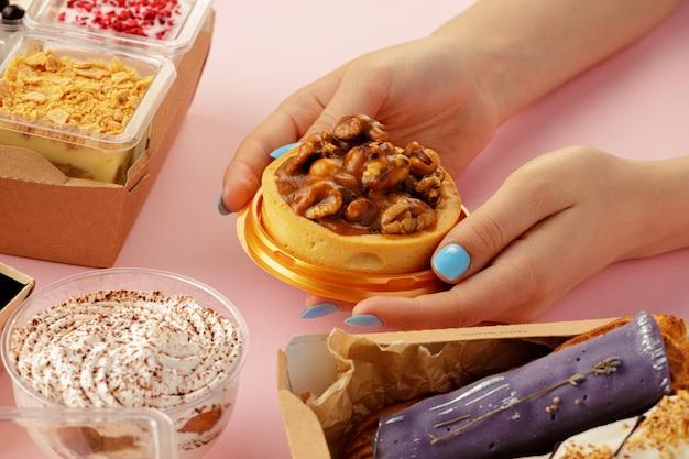 新鮮な菓子の中で手でデザートを保持している女性の手
