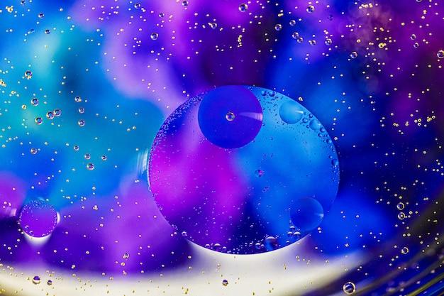 オイルサークルと青色の背景。水の泡。閉じる。
