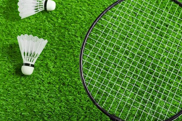 羽根とバドミントンラケットの緑の芝生