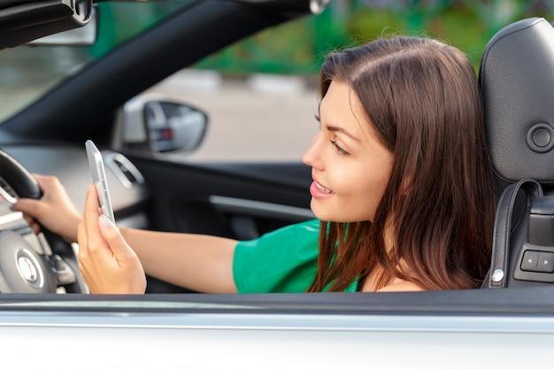 ビジネスの女性が車の中で座っていると彼女のスマートフォンを使用しています。
