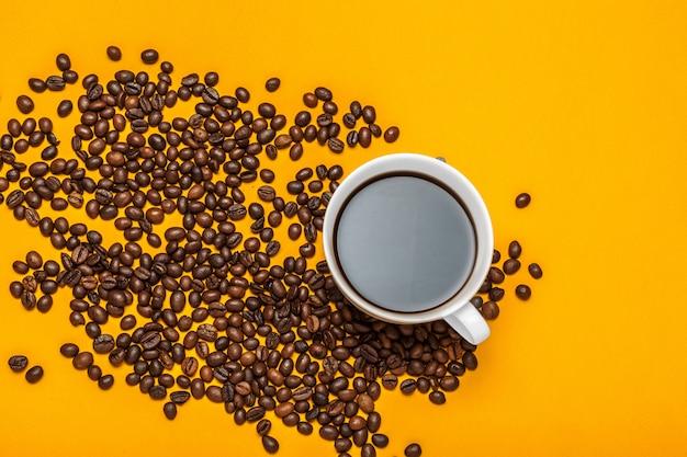 Пролитый кофе в зернах на ярко-желтый