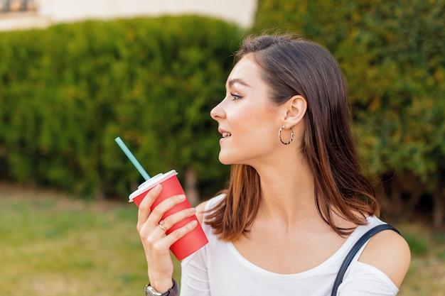 晴れた日に通りでドリンクを飲みながら若い魅力的な女性