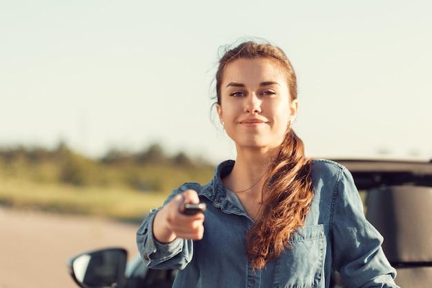 Молодая милая женщина стоя около автомобиля с откидным верхом с ключами в руке