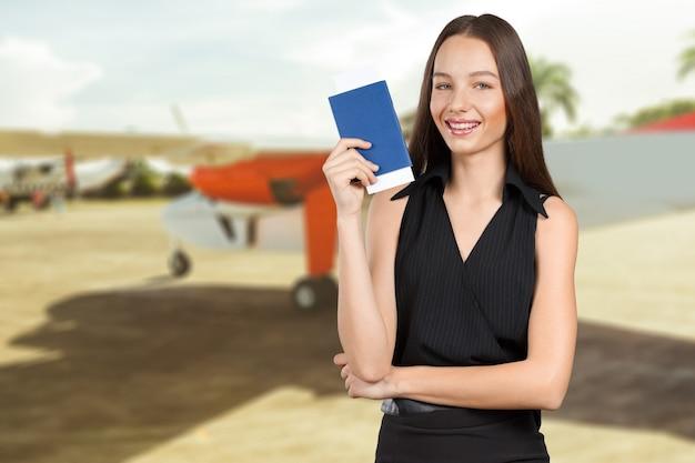 パスポートを保持している幸せな観光女の肖像