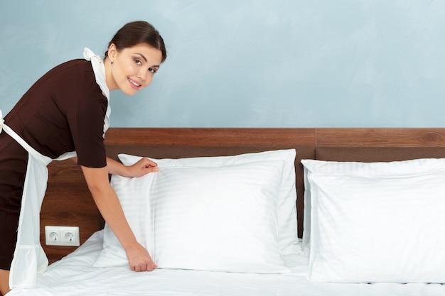 ホテルの部屋でベッドを作る若いメイド