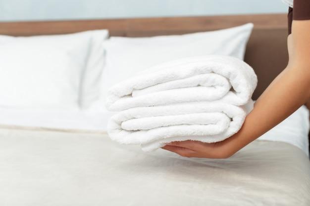 ホテルの部屋での清掃中に新鮮な清潔なタオルでメイド