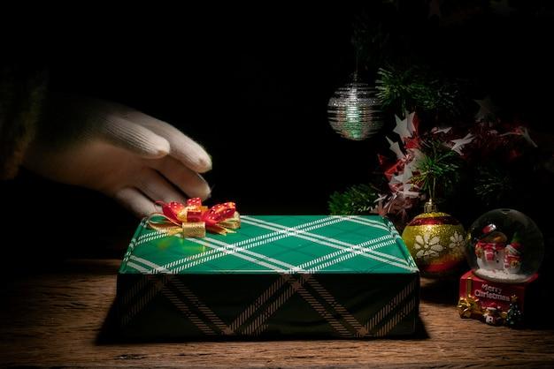 手サンタは木のテーブルにギフトボックスを置くギフトボックスとライトの装飾