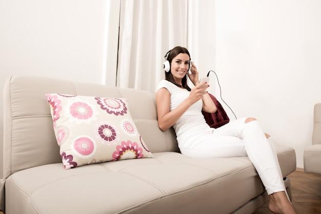 音楽を聞くヘッドフォンで美しい若い女性