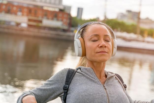 橋の欄干の横で音楽を聴く運動の女性