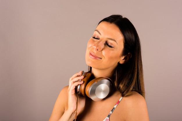 ヘッドフォンのペアを持つ笑顔の女性の肖像画