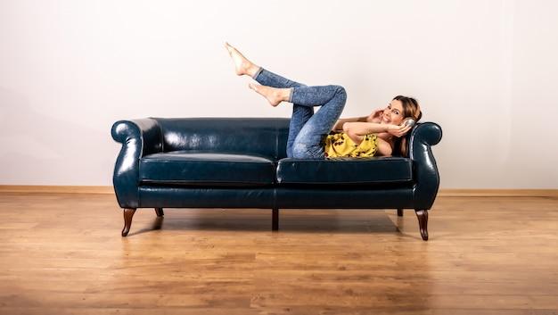 ソファーでポーズしながら音楽を聴く女性
