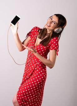 スマートフォンの画面を見せる若い女性