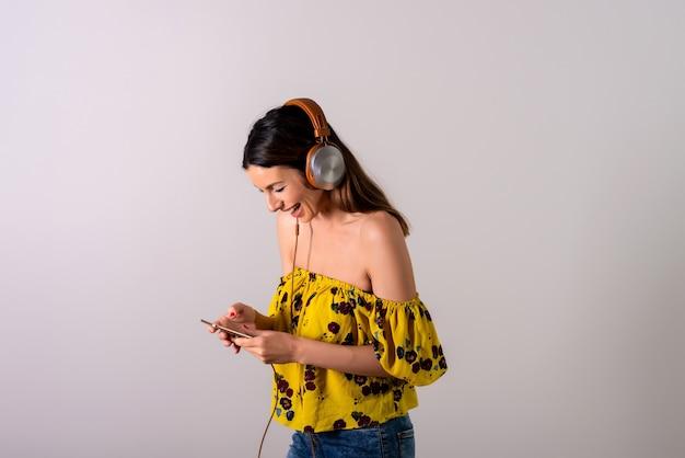 スマートフォンを使用して黄色のドレスを着た幸せな若い女性