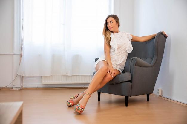 成熟した女性が椅子でポーズの官能的な写真