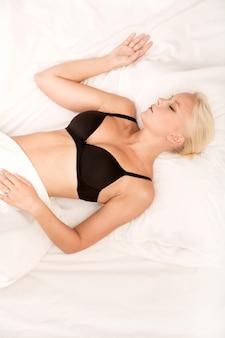彼女のベッドで横になっている下着の女