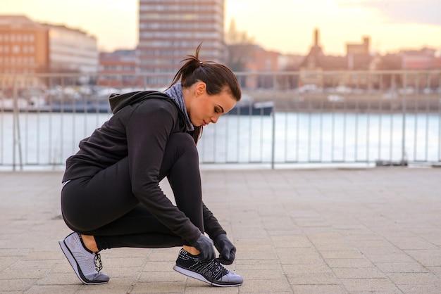 Спортивная молодая женщина завязывает шнурки