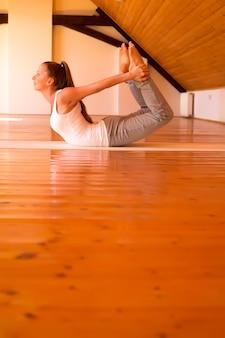 Женщина занимается йогой в студии