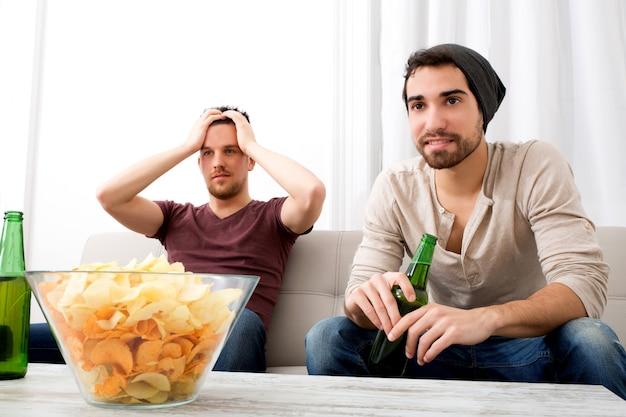 Двое друзей смотрят телевизор дома