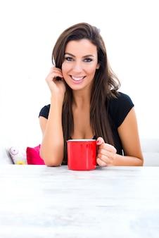 家でコーヒーを飲む若い美しい女性
