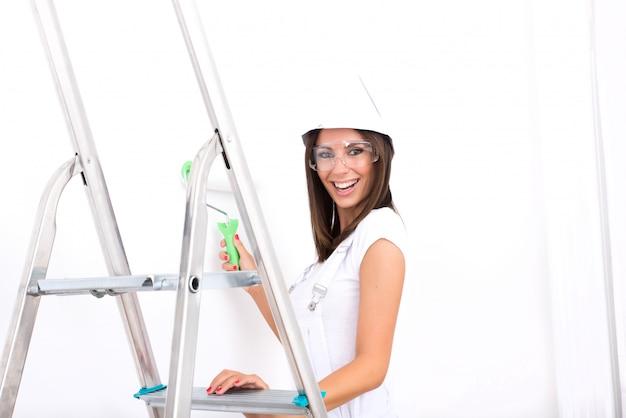 アパートを塗る美しい若い女性