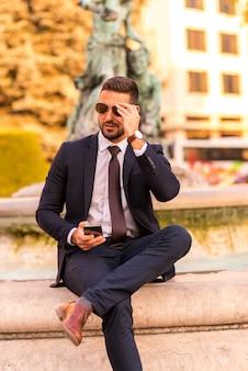 座ってスマートフォンを使うビジネスマン
