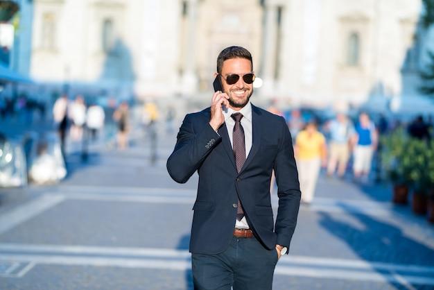 歩くと彼の電話で話しているビジネスマン