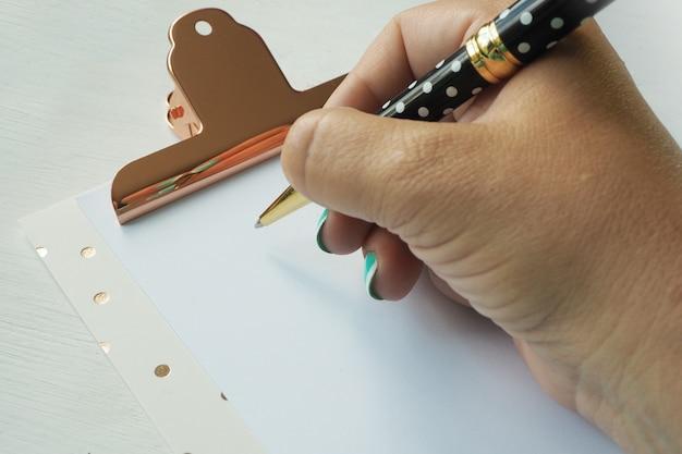 女性の手がクリップボードのきれいな紙にボールペンで書き込みます。