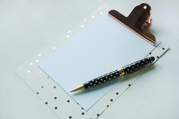 白いテーブルにクリップボードと黒白い水玉ペンのモックアップを作成します。