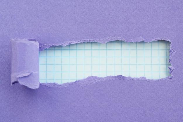 紫色の紙と背景の市松模様の紙の破れたエッジを持つ穴。テキスト用のスペース。