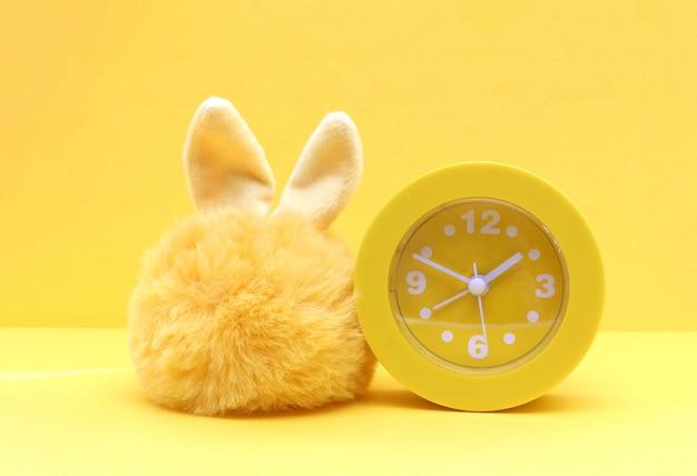 Желтый игрушка меховой заяц и желтые пластиковые часы на желтом фоне бумаги. копировать пространство.