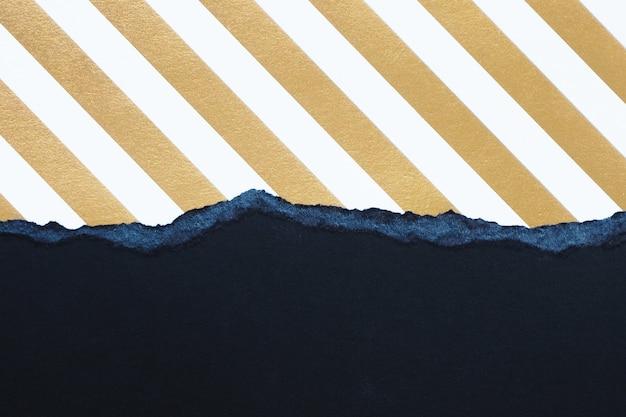 抽象的な背景とテクスチャー。引き裂かれた黒い段ボールとストライプの金と白の紙。