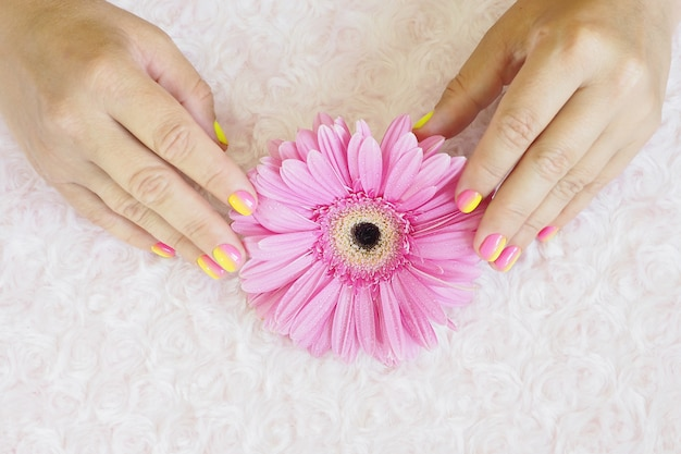 明るいピンクと黄色のグラデーションマニキュアで女性の手