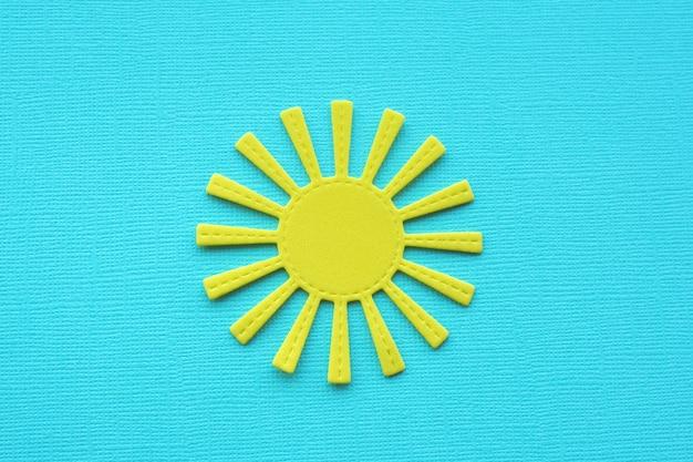 Яркое желтое солнце на голубой фактурной бумаге.