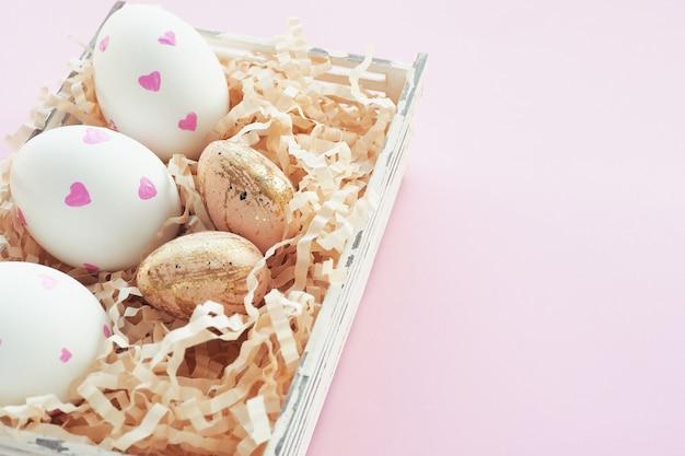 Пасхальные белые яйца с розовыми сердечками и бежевый в черное пятнышко и золотые штрихи в корзине на розовом фоне.