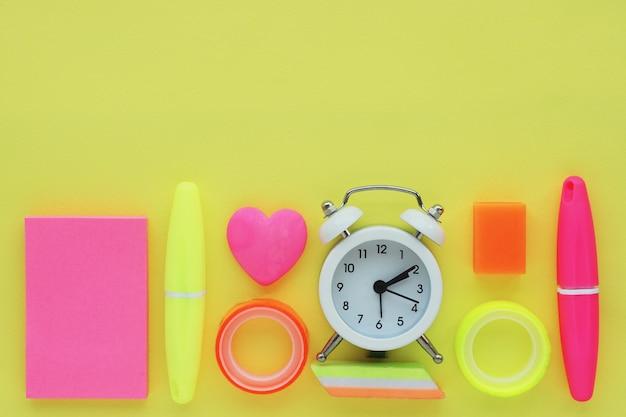 文房具:マーカー、ステッカー、目覚まし時計、さまざまな形の消しゴム、色付きテープ。フラットレイアウト、黄色の背景の平面図。テキスト用のスペース。