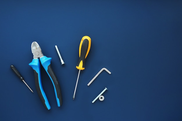 ツールペンチ、ドライバー、レンチ、ボルト、セルフタッピングネジ、暗い青色の背景のナット。テキスト用のスペース。