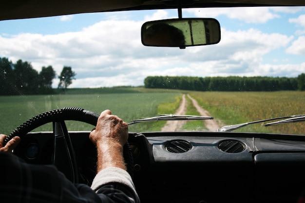 乗用車のステアリングホイールと道路、雲、森、フィールドの前に隠れているシャツで日焼けした男性の手。