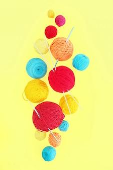 黄色の背景に浮かぶさまざまなサイズのウール糸のマルチカラーのボール。