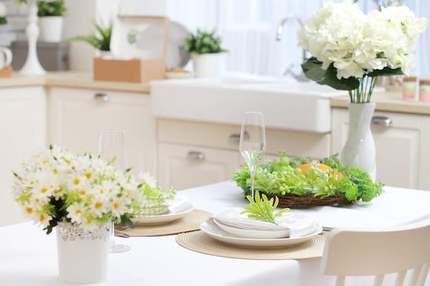 白いテーブルクロス、花、グラス、プレートを備えたダイニングテーブル。窓際に沈む。