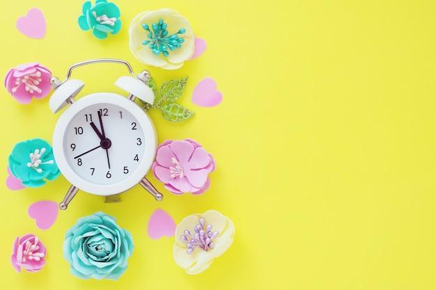 明るい黄色の背景に白い小さな目覚まし時計と多くのマルチカラーの造花。テキストのためのスペース。