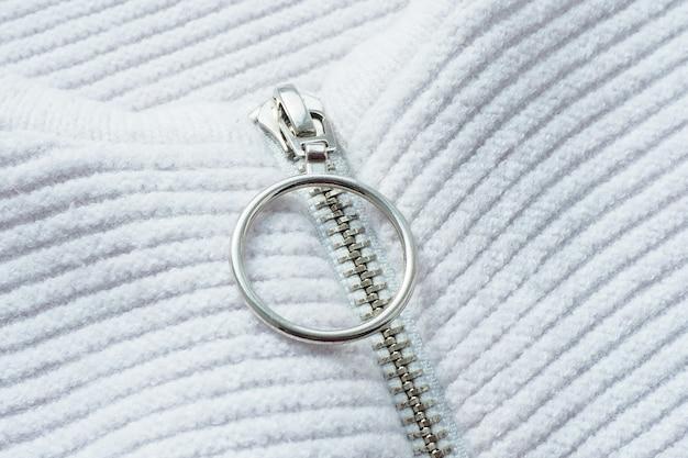 Абстрактная предпосылка и текстура вязаной белой куртки с застежкой-молнией и застежкой с металлическим кольцом.