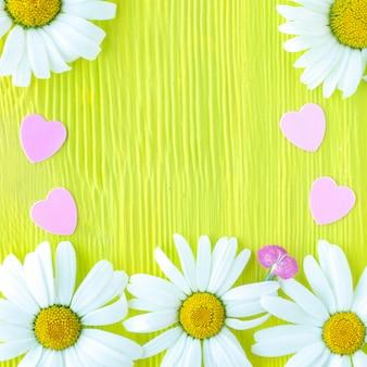 Цветы ромашки и пластиковые розовые сердца на желто-зеленой деревянной текстуре фона. копировать пространство.