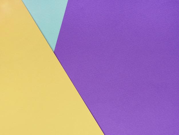 水彩紙の薄紫色の黄色と青のシートの抽象的な幾何学的な背景