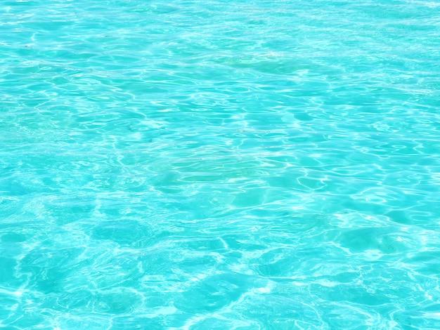 Предпосылка и текстура воды бирюзы волнистой в бассейне на солнце.